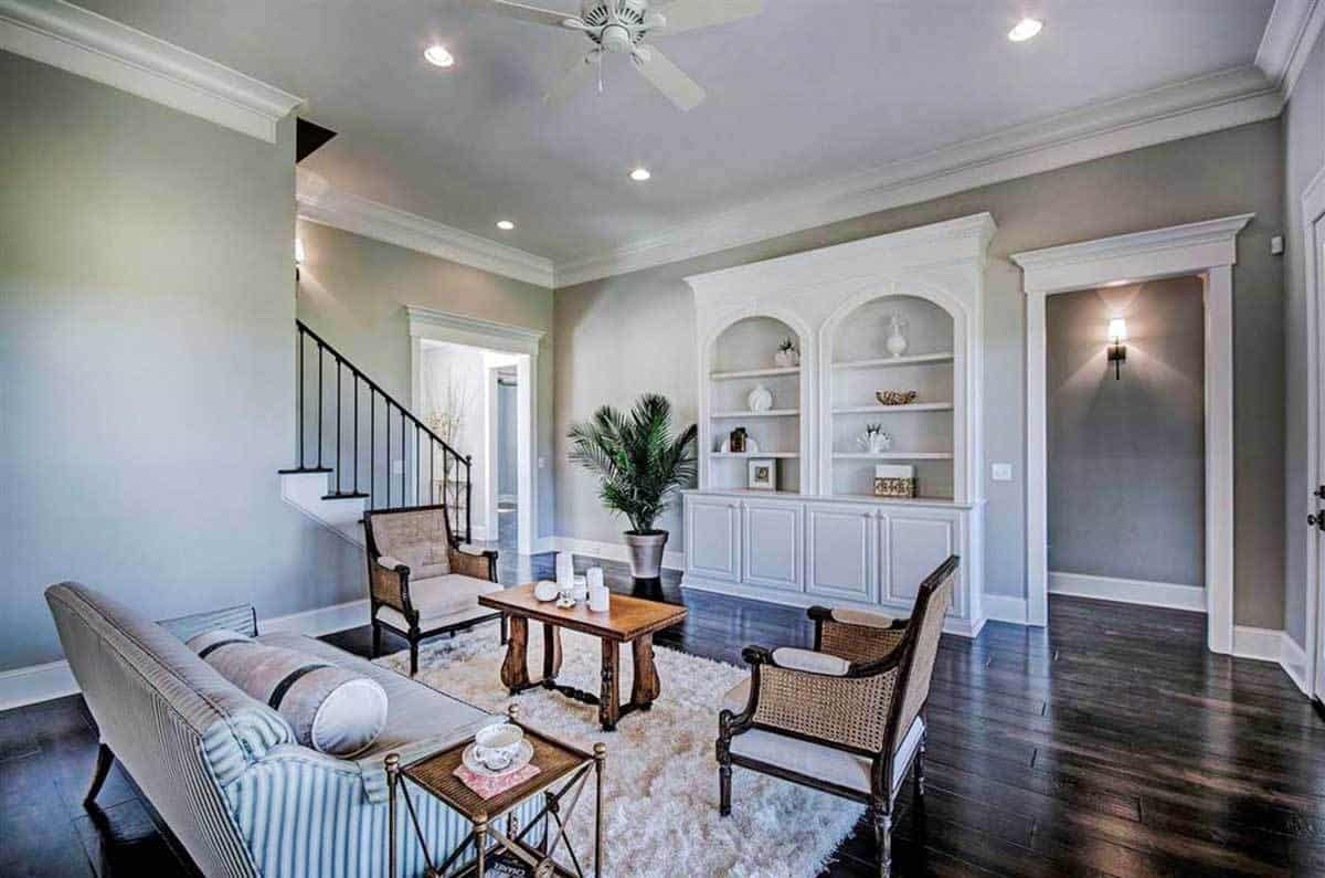 A striped sofa, wicker seats, wooden coffee table, beige shaggy rug, and arched built-ins completed the living room.