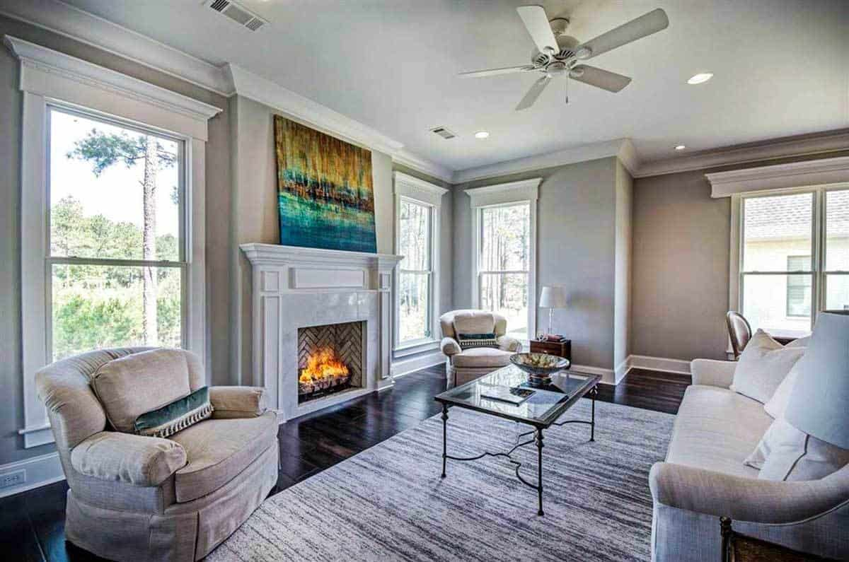 Keeping room with gray skirted seats, a glass top coffee table and a marble fireplace accented with a gorgeous painting.
