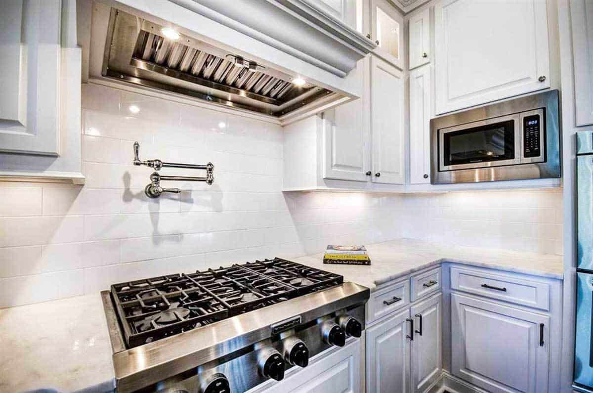 Cooking range nestled in between the white cabinetry and marble countertops.