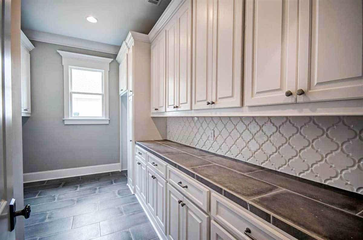 The utility room is filled with white cabinets and a tiled countertop matching with the brick flooring.
