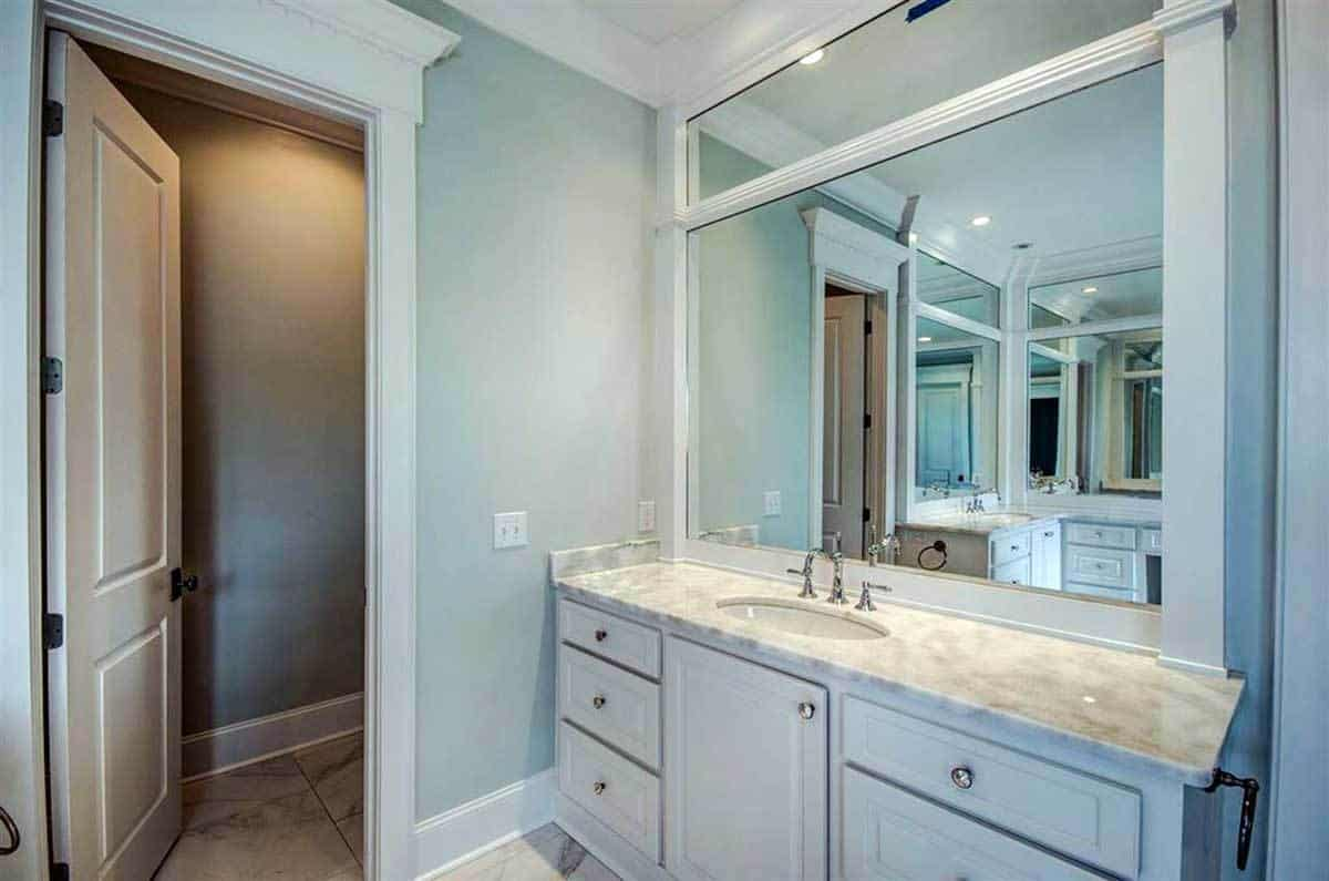 Opposite side view of the primary bathroom shows the water closet and sink vanity paired with a large mirror.