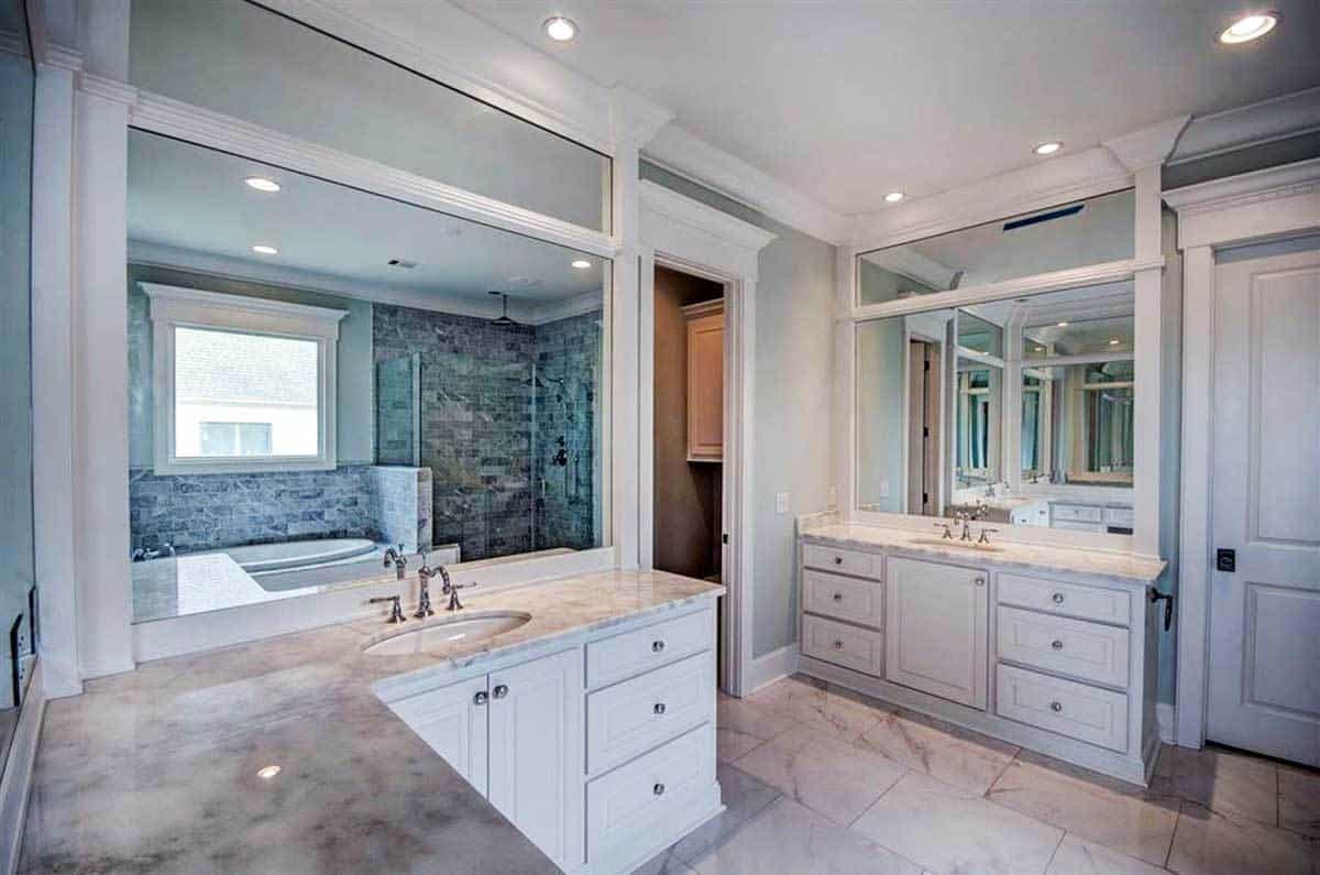 A farther view shows an L-shaped vanity with marble countertops and an undermount sink.