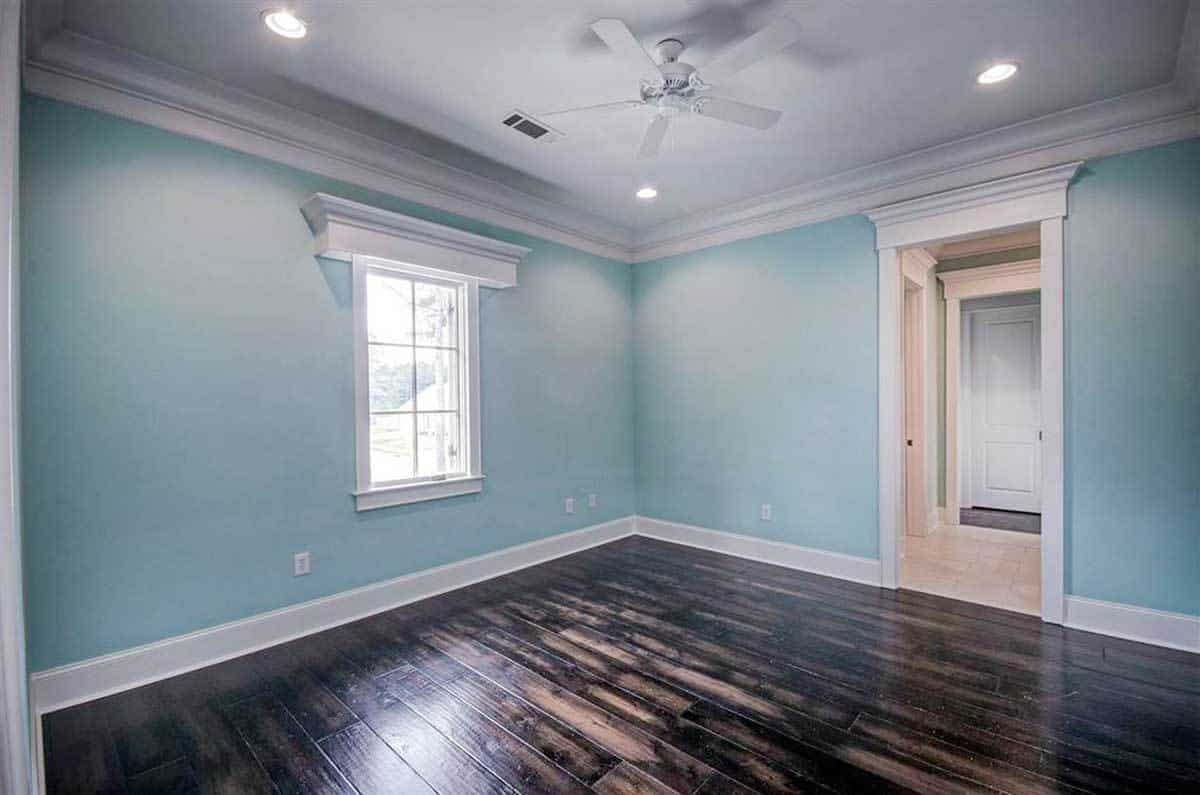 This bedroom has light blue walls, dark hardwood flooring and a small window that lets natural light in.