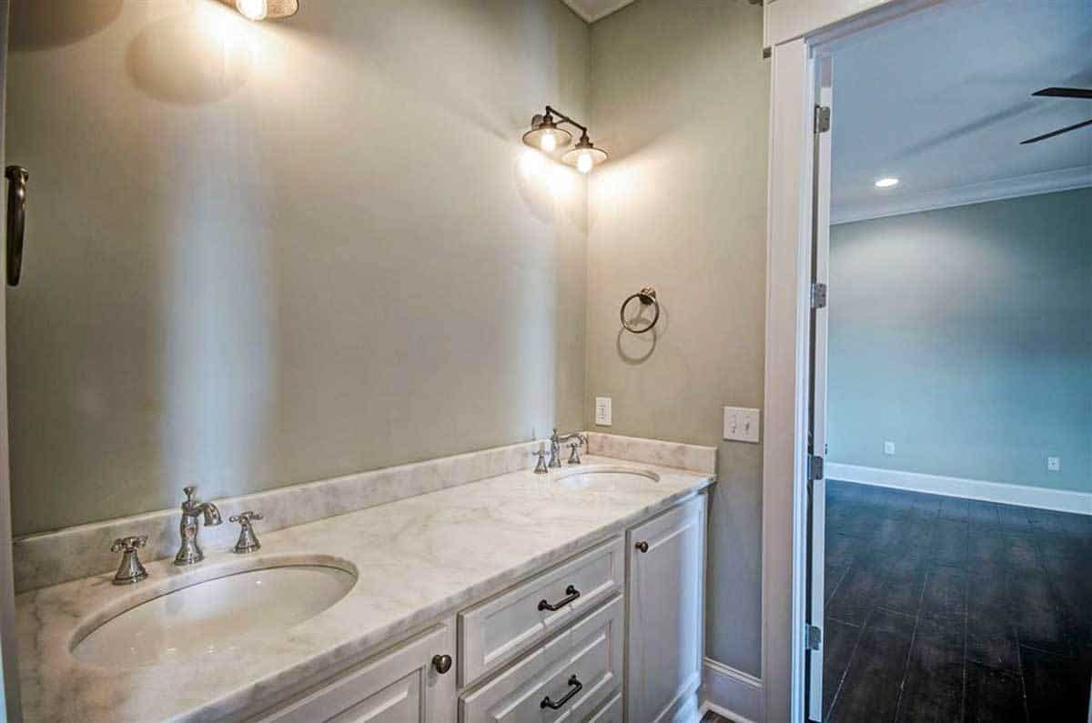 The bathroom boasts a dual sink vanity illuminated by warm dome sconces.