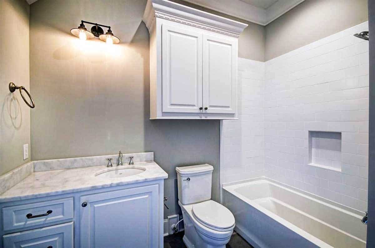 The bathroom offers a tub and shower combo, a toilet, and a marble top vanity lit by dome sconces.