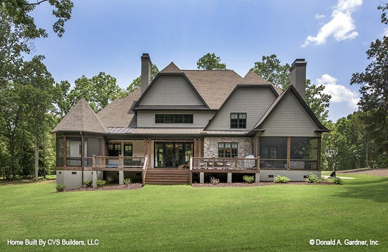 Home's rear view with gray exterior siding, stone accents, and a back deck flanked by screened porches.