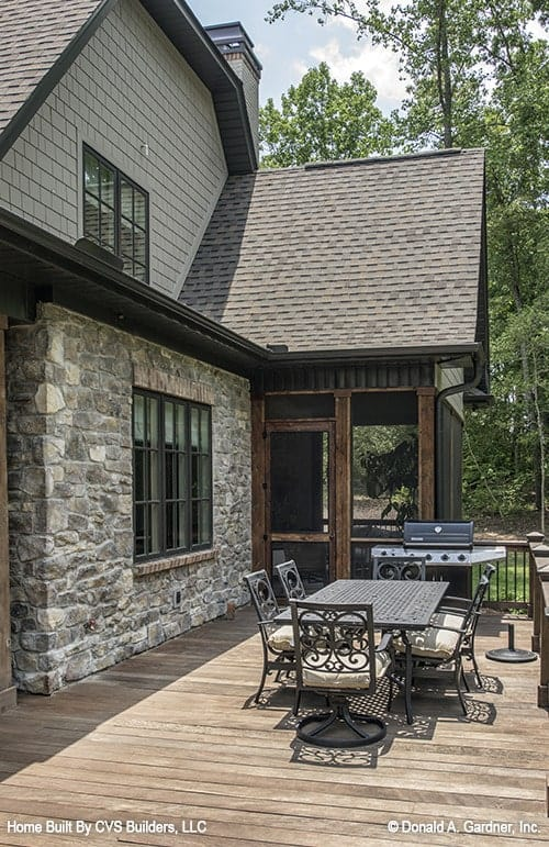 A closer look at the deck shows the outdoor grilling and a metal dining table surrounded by cushioned chairs.