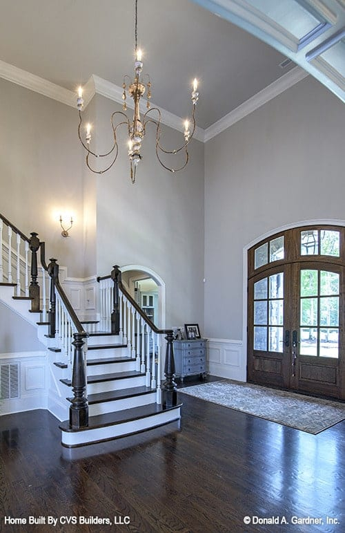 The foyer has an arched french entry door and a staircase illuminated by a warm chandelier.