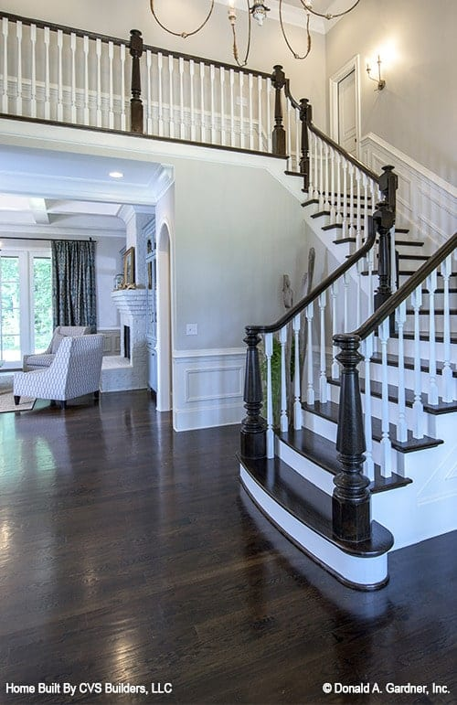 Next to the traditional staircase with dark wood railings is the living room.