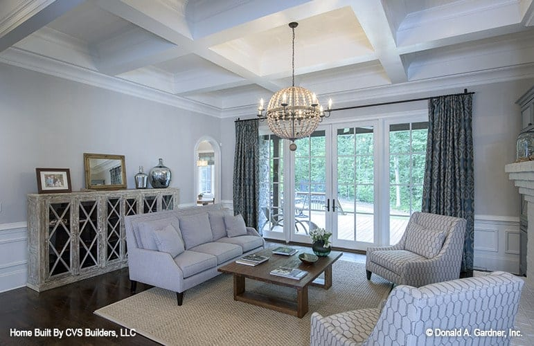 Living room with coffered ceiling and a french door leading out to the rear deck.
