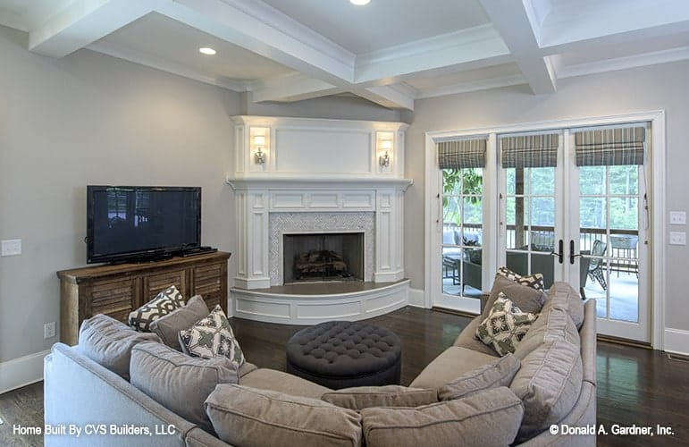 Hearth room with a curved sectional, a flat-screen TV, and a corner fireplace lit by warm sconces.