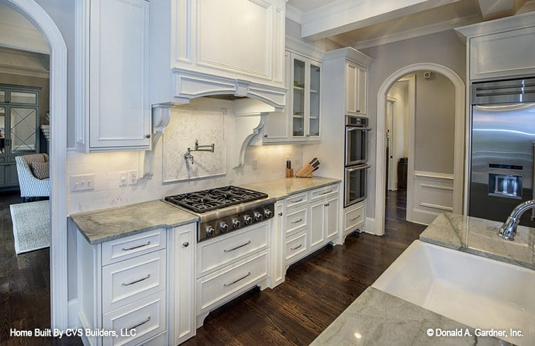 The kitchen has stainless steel appliances and white cabinetry that matches the marble tiled backsplash.
