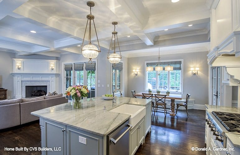 The center island is fitted with an oven and a farmhouse sink paired with a gooseneck faucet.