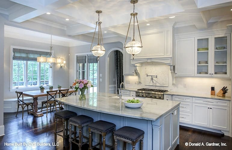 The breakfast nook is situated beside the kitchen and by the glass-paneled windows dressed with blue striped valances.