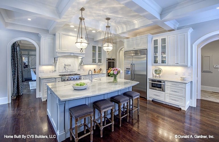 The kitchen has natural hardwood flooring and a coffered ceiling mounted with spherical glass pendants.