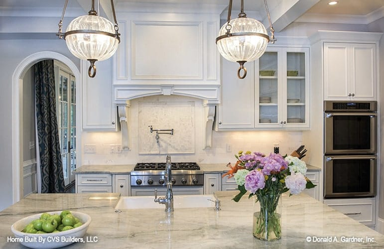 A closer view shows the granite top island, double wall oven, and a cooking range under the bespoke vent hood.