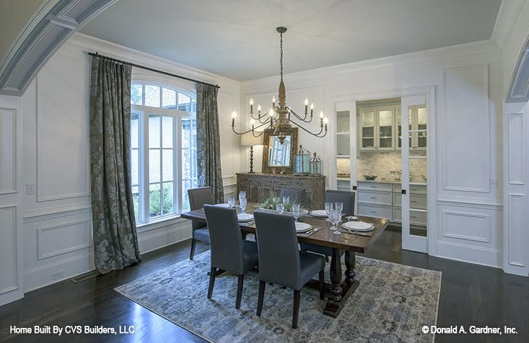 Formal dining room with a vintage chandelier, wooden buffet bar, and a rectangular dining set sitting over the patterned area rug.