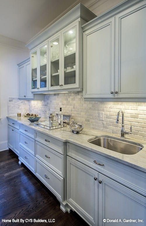 A closer look at the butler's pantry shows the white cabinets and undermount sink fitted on the marble counter.