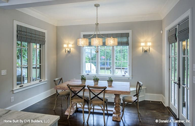Breakfast nook with wicker chairs and a natural wood dining table illuminated by drum pendants.