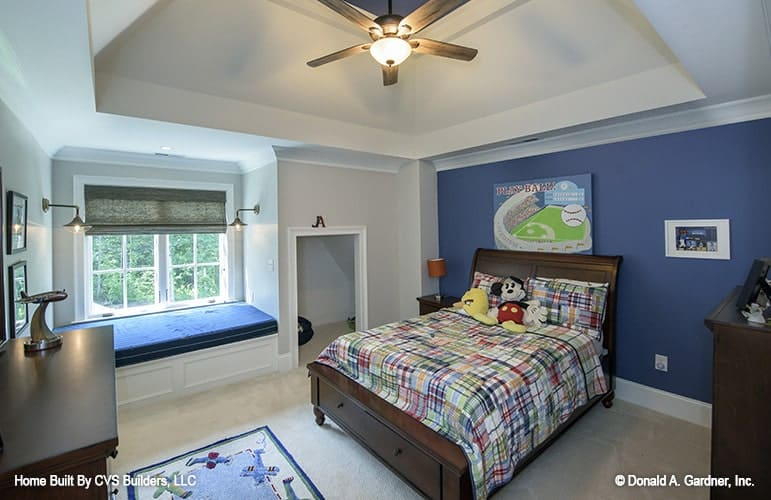 Boy's bedroom with a window seat nook, wooden furniture, and blue accent wall adorned by various artworks.