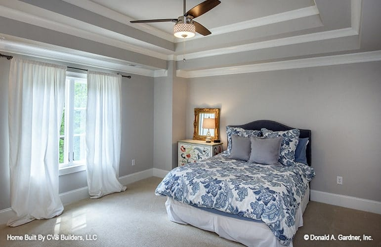 This bedroom has a beige carpet flooring and gray walls matching with the step ceiling.