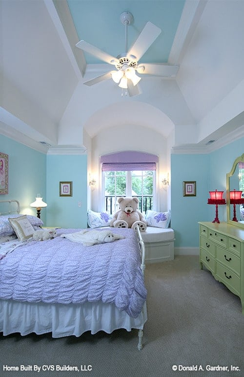 Girl's bedroom with a vaulted ceiling, green dresser, white metal bed, and an alcove window seat topped with charming pillows and a cute teddy bear.