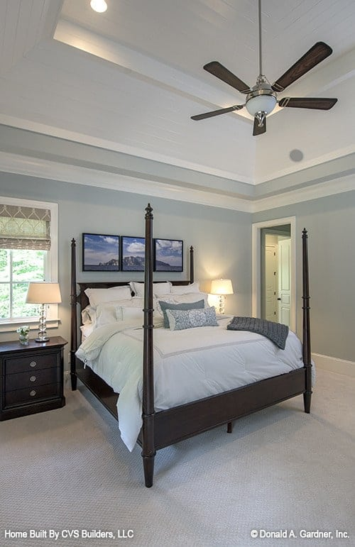 The primary bedroom features a high tray ceiling and a four-poster bed over beige carpet flooring.