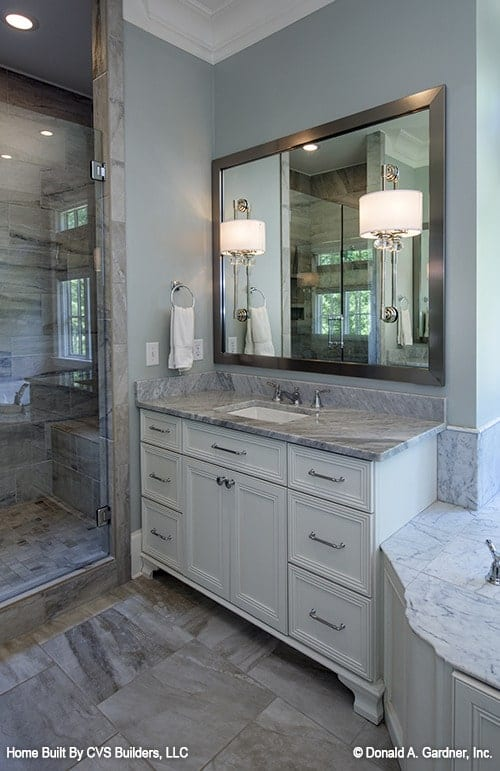 Sink vanity with white drawers and a marble countertop matching with the tiled flooring.