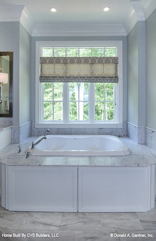A deep soaking tub under the white framed window dressed in a patterned roman shade.