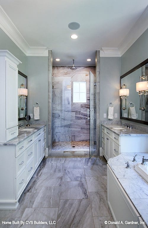 The primary bathroom offers a walk-in shower and facing sink vanities lit by warm sconces.