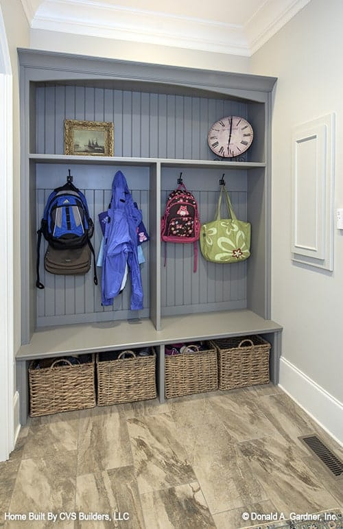 The mudroom has marble tiled flooring and built-in storage filled with hooks and rattan baskets.