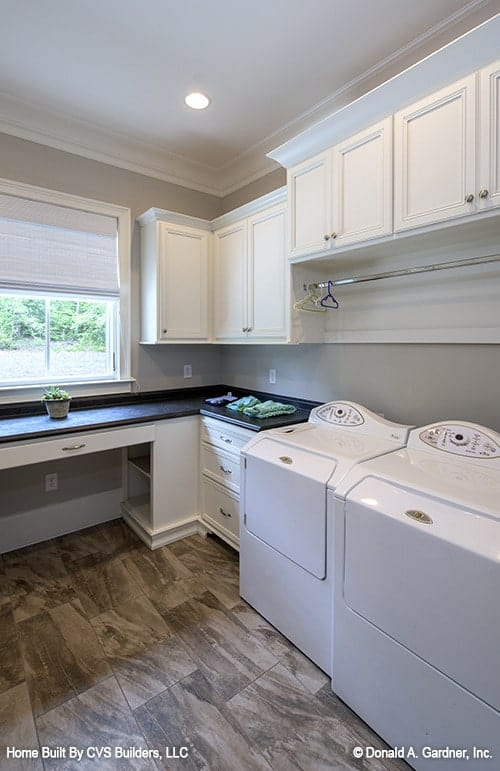 The utility room is equipped with black granite counter and white appliances matching with the floating cabinets.