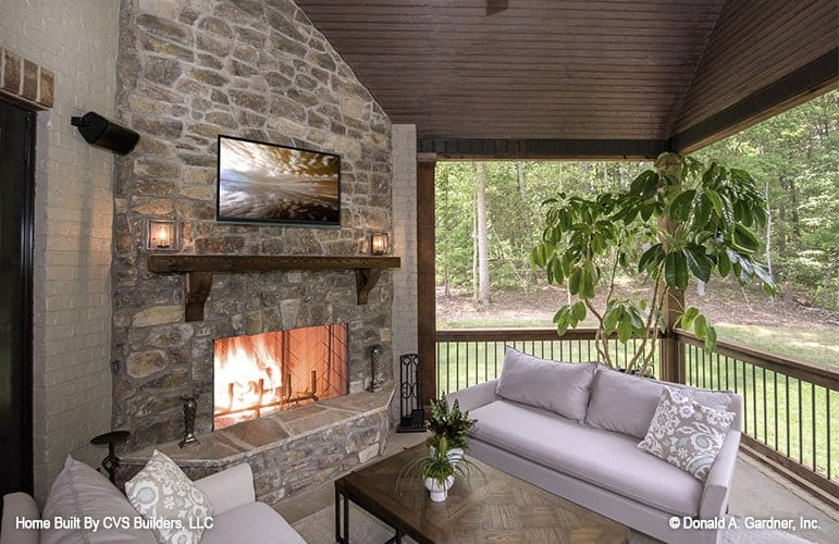 Screened porch with gray sofas and a rectangular coffee table facing the stone fireplace and wall-mounted TV.