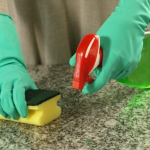 A pair of gloved hands cleaning the granite countertop with a sponge and sprayer.