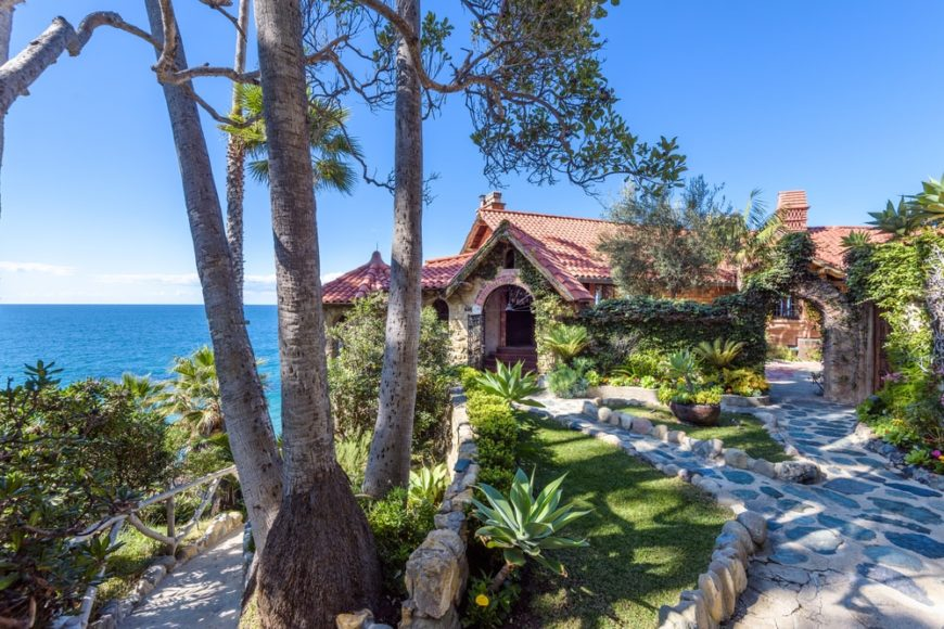 This beautiful home is perched on a cliff overlooking the ocean foregrounded with a beautiful landscaping that augments the beauty of the Mediterranean-style house with stucco roofs. Images courtesy of Toptenrealestatedeals.com.