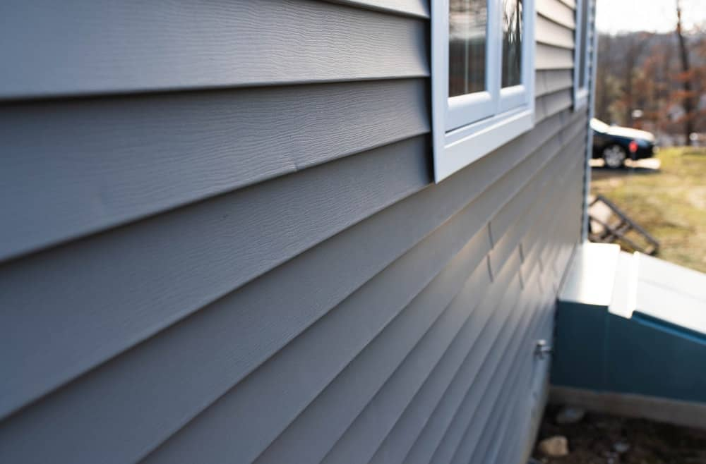 Close up of a home with gray vinyl siding.