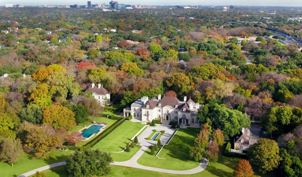 This is an aerial view of the large property. Here you can see the main home surrounded by tall trees and lush green lawns and beside it is a separate guest house almost hidden by tall trees. Images courtesy of Toptenrealestatedeals.com.