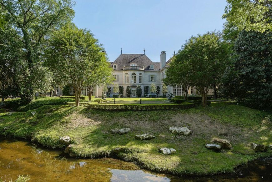 This is the view of the back of the house from the vantage of the beautiful creek paired with a lush landscaping filled with grass, shrubs and tall trees that complement the exterior of the house that has large windows, arches and tall chimneys. Images courtesy of Toptenrealestatedeals.com.