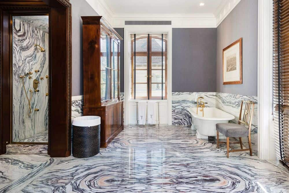 This other bathroom has a more detailed marble flooring that extends to the backsplash of the bathtub placed at the corner across from the wooden cabinet. Images courtesy of Toptenrealestatedeals.com.