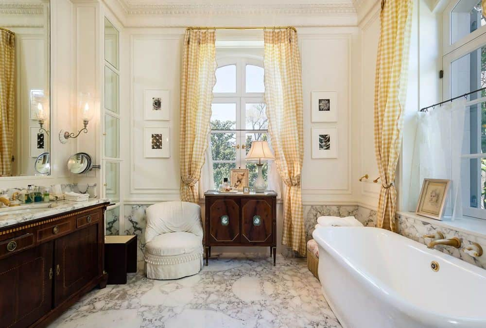 This gorgeous bathroom has a dark wooden vanity across from the freestanding porcelain bathtub that complements the marble flooring. Images courtesy of Toptenrealestatedeals.com.