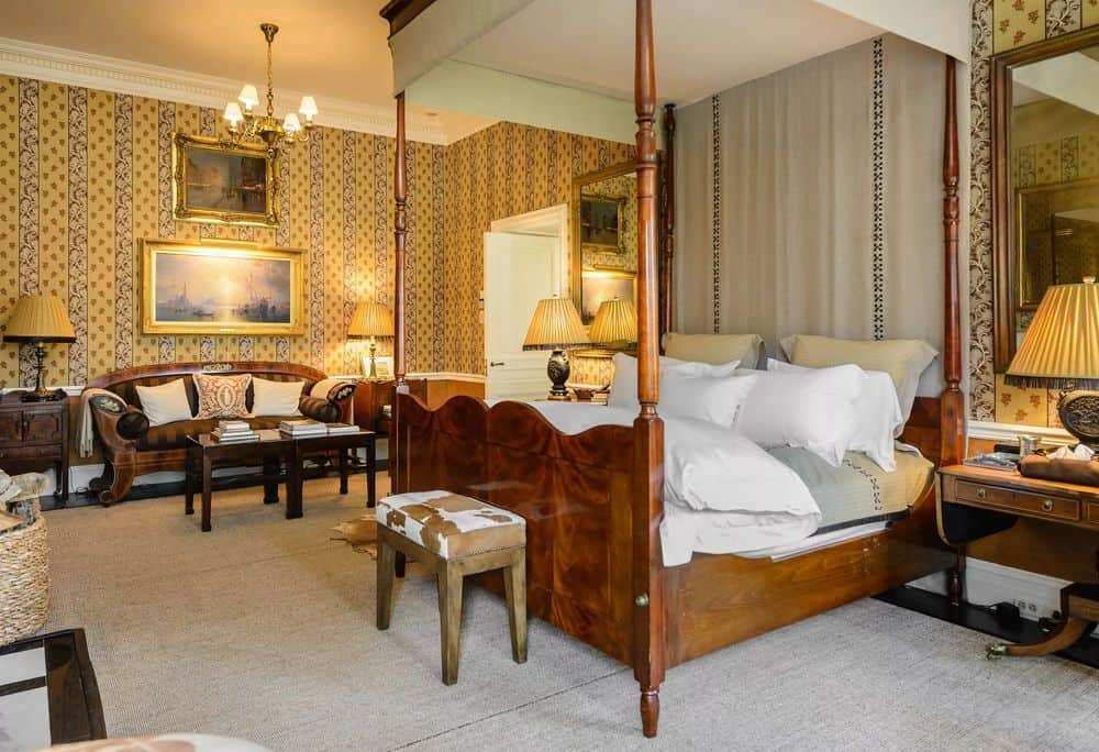 This other bedroom has a lovely wooden four-poster bed that stands out against the carpeted flooring and beige walls warmed by the yellow lights of the lamps. Images courtesy of Toptenrealestatedeals.com.