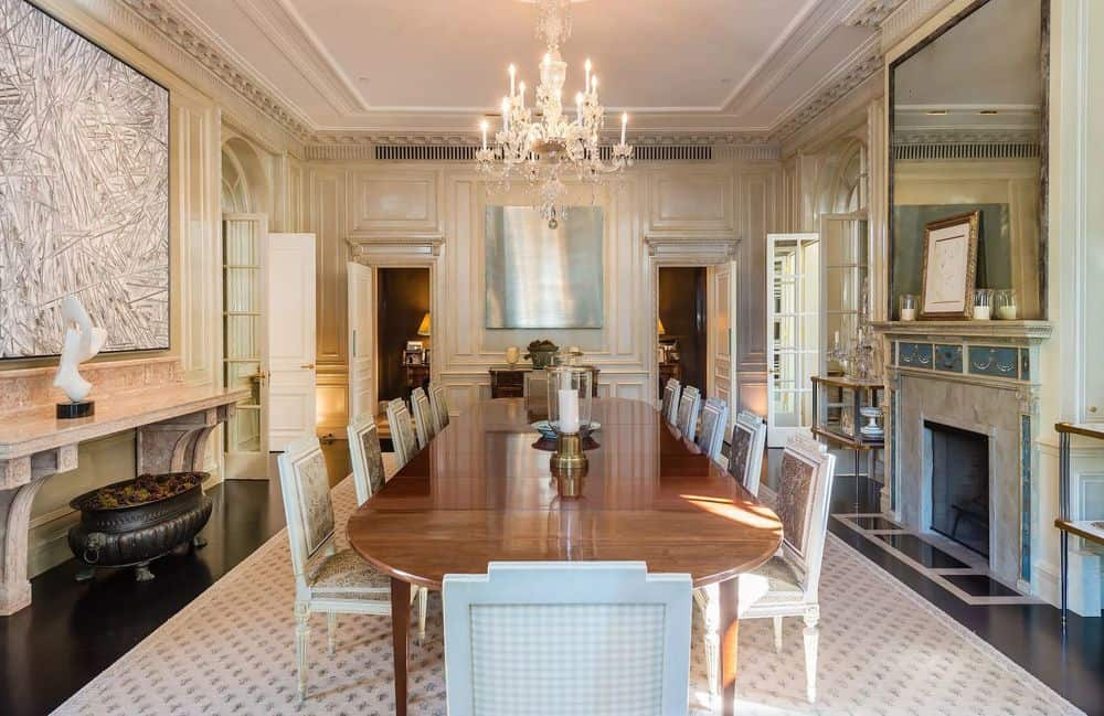 The large wooden dining table of this formal dining room is topped with a n elegant crystal chandelier hanging from a white tray ceiling. Images courtesy of Toptenrealestatedeals.com.