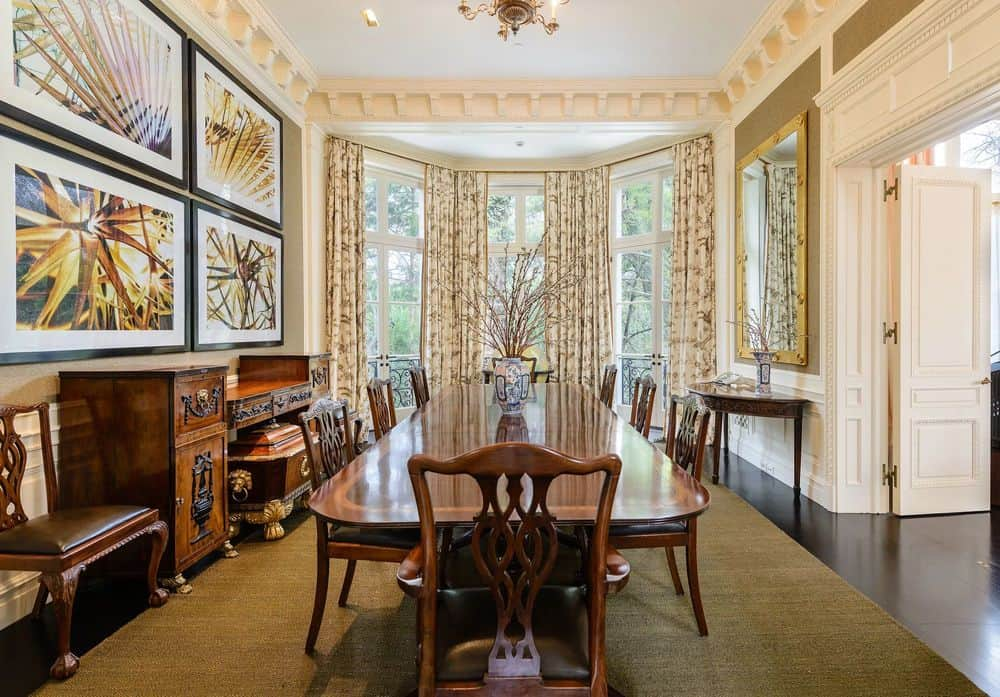 This is the formal dining area with an elegant brown wooden dining table paired with wooden chairs complemented by the natural lighting that comes in through the tall curtained windows at the far end. Images courtesy of Toptenrealestatedeals.com.