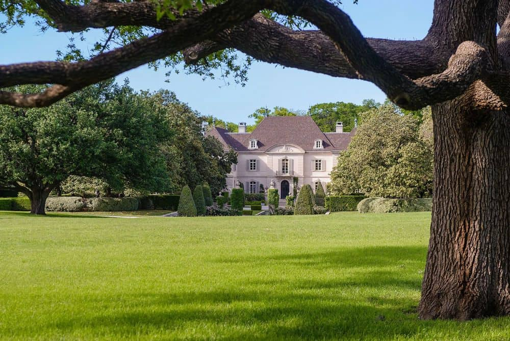 This view of the house from a distance boasts of the massive lawn of well-maintained grass of the estate bordered with multiple tall trees that are even bigger than the house itself. Images courtesy of Toptenrealestatedeals.com.