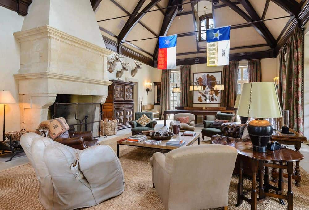 This living room has a tall arched ceiling with exposed wooden beams paired with a warm and homey large fireplace housed by a massive stone structure that reaches to the ceiling across from the comfortable sofas. Images courtesy of Toptenrealestatedeals.com.