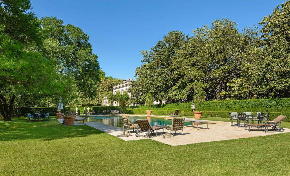 This is the large pool of the estate surrounded by lush green lawns of grass and several sitting areas to better enjoy the pool side under the shade of tall trees. Images courtesy of Toptenrealestatedeals.com.