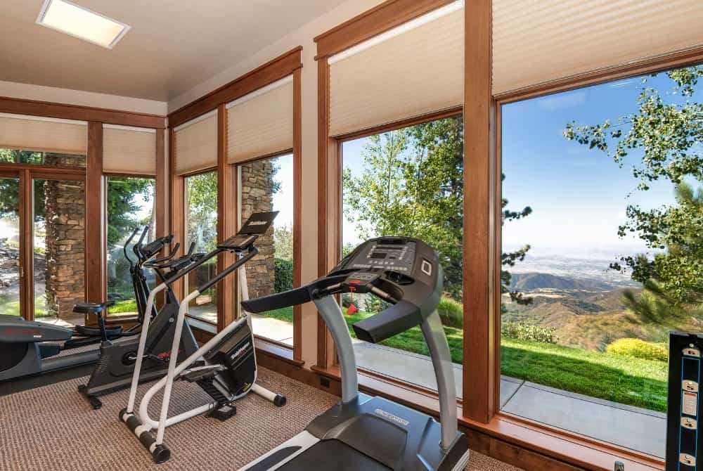 Here's a look at some of the homy gym's equipment set near the tall glass windows. Images courtesy of Toptenrealestatedeals.com.
