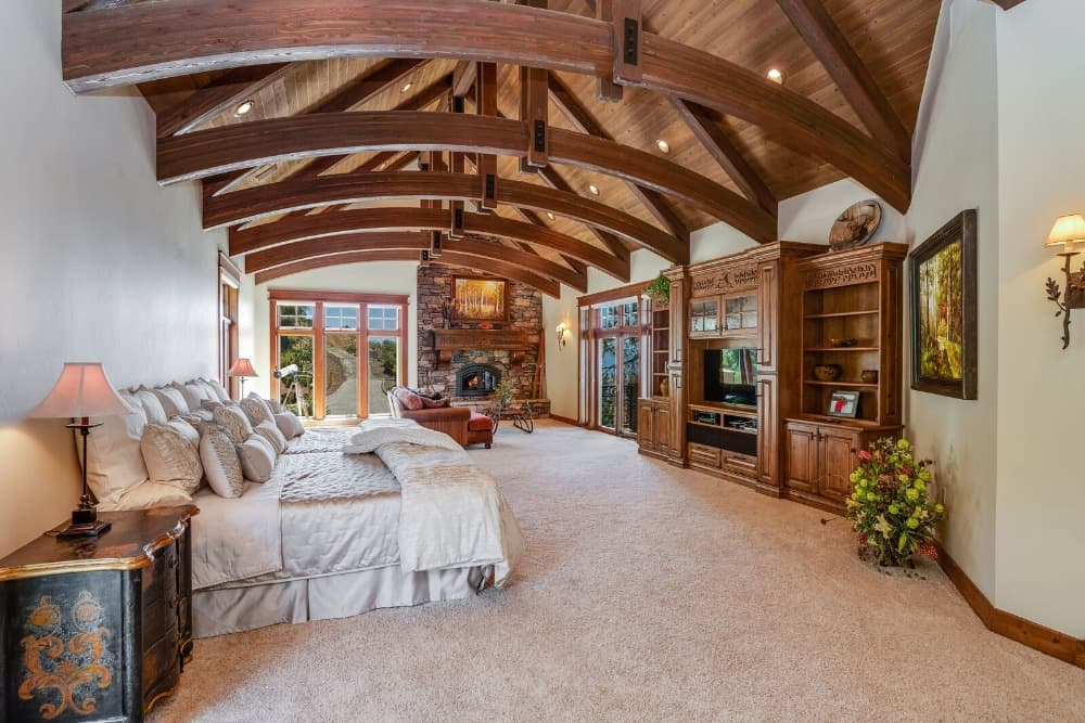A spacious primary bedroom with a large cozy bed and a stone fireplace on the side. The room features carpeted flooring and a vaulted ceiling with large exposed beams. Images courtesy of Toptenrealestatedeals.com.