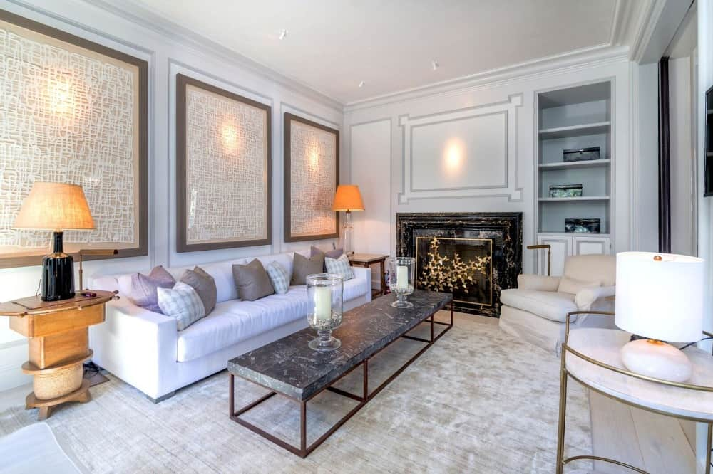 This living space offers a white couch and a stylish center table, along with a classy fireplace. Images courtesy of Toptenrealestatedeals.com.
