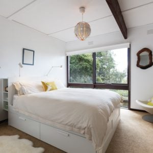 A lovely guest bedroom with white walls and ceiling.